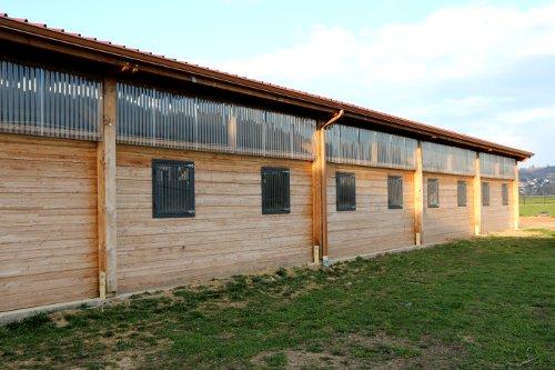 Fenêtres de boxes pour chevaux vues de l'extérieur du bâtiment