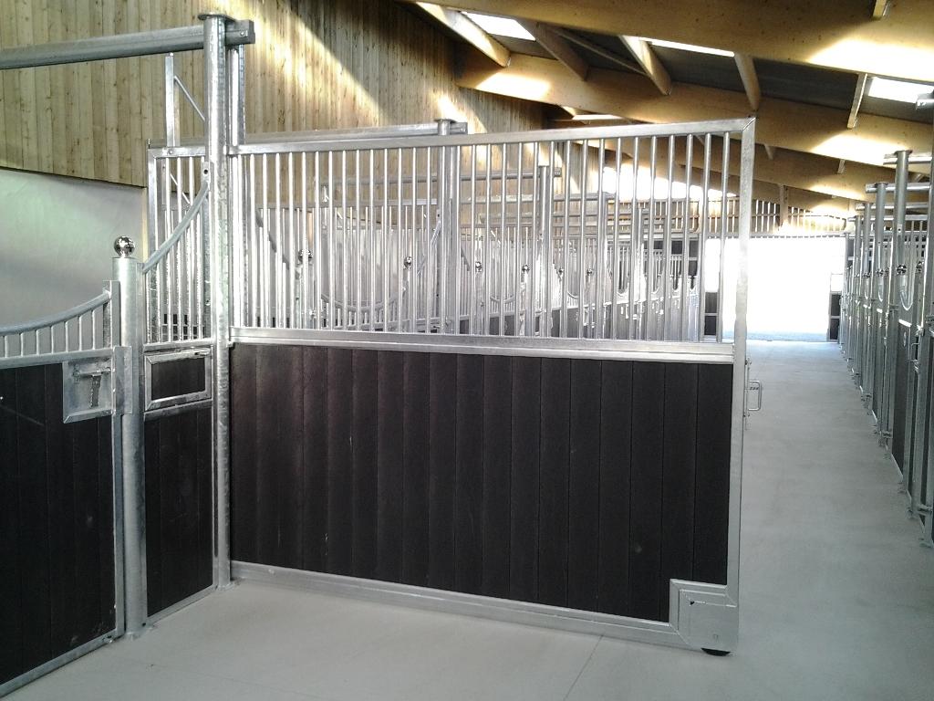 Cloison coulissante dans l'allée centrale d'une écurie pour chevaux