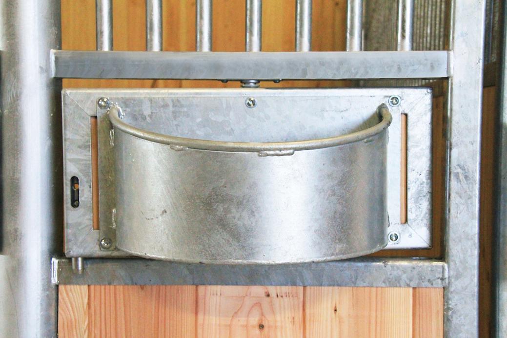 Mangeoire pivotante ouverte sur une façade de box pour cheval