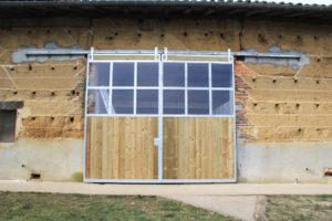 Grand portail de grange fermé en bois et Plexiglas